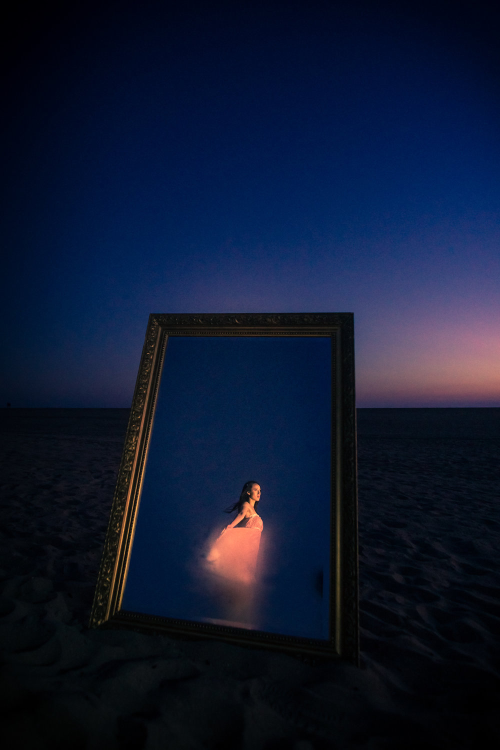 Experimental portrait with a vintage mirror with a lady a in a pink dress taken on the beach on Balboa Peninsula