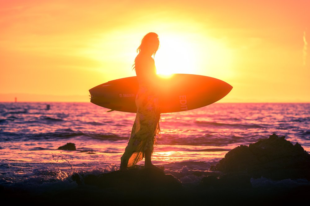 Hey beautiful artistic surfer girl portrait of her silhouette while she is holding her surfboard at the little beach tidepools in Orange County with an orange and purple sunset