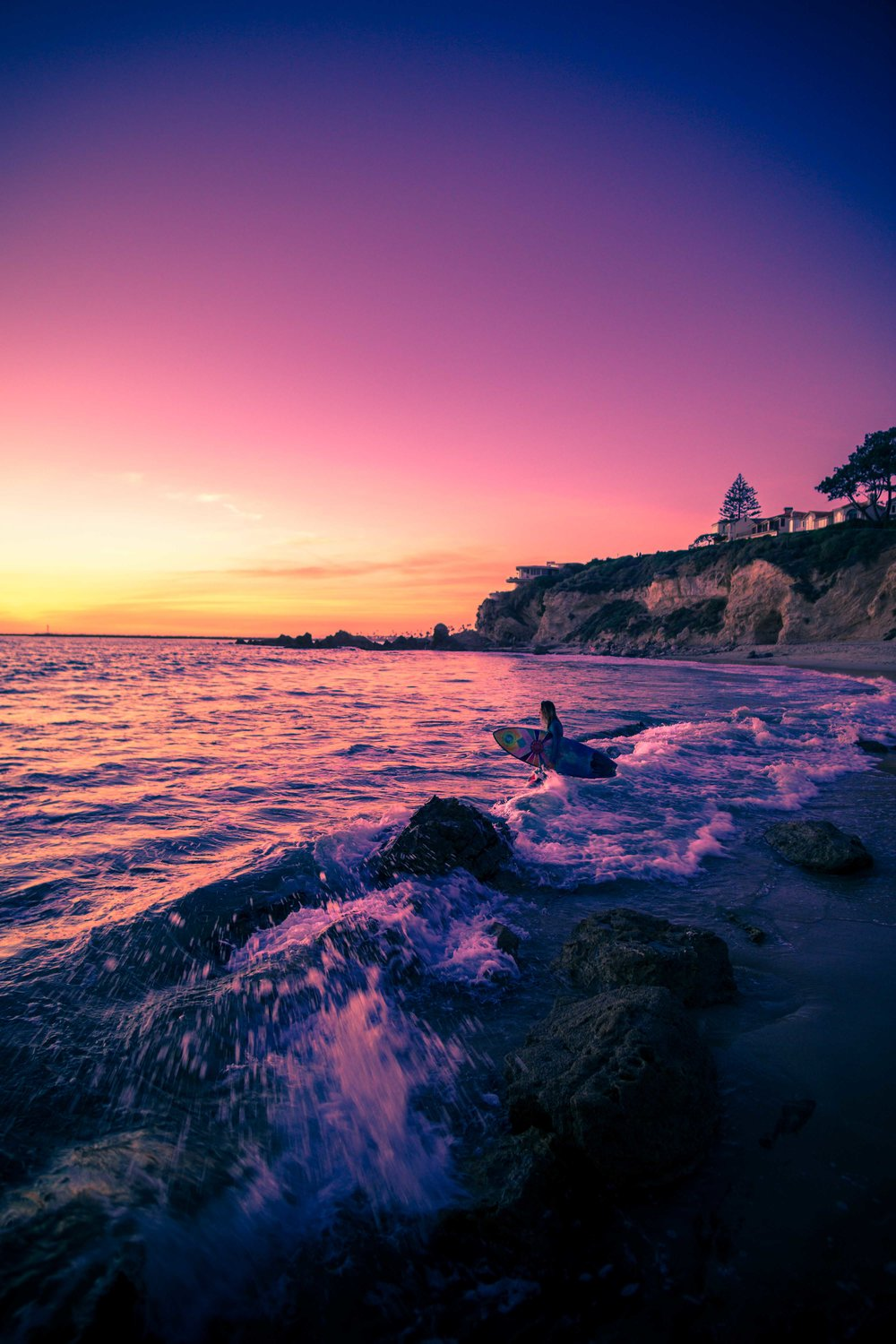 Wide angle photo of a surfer girl walking out to the waves at Corona Del Mar beach during Sunset