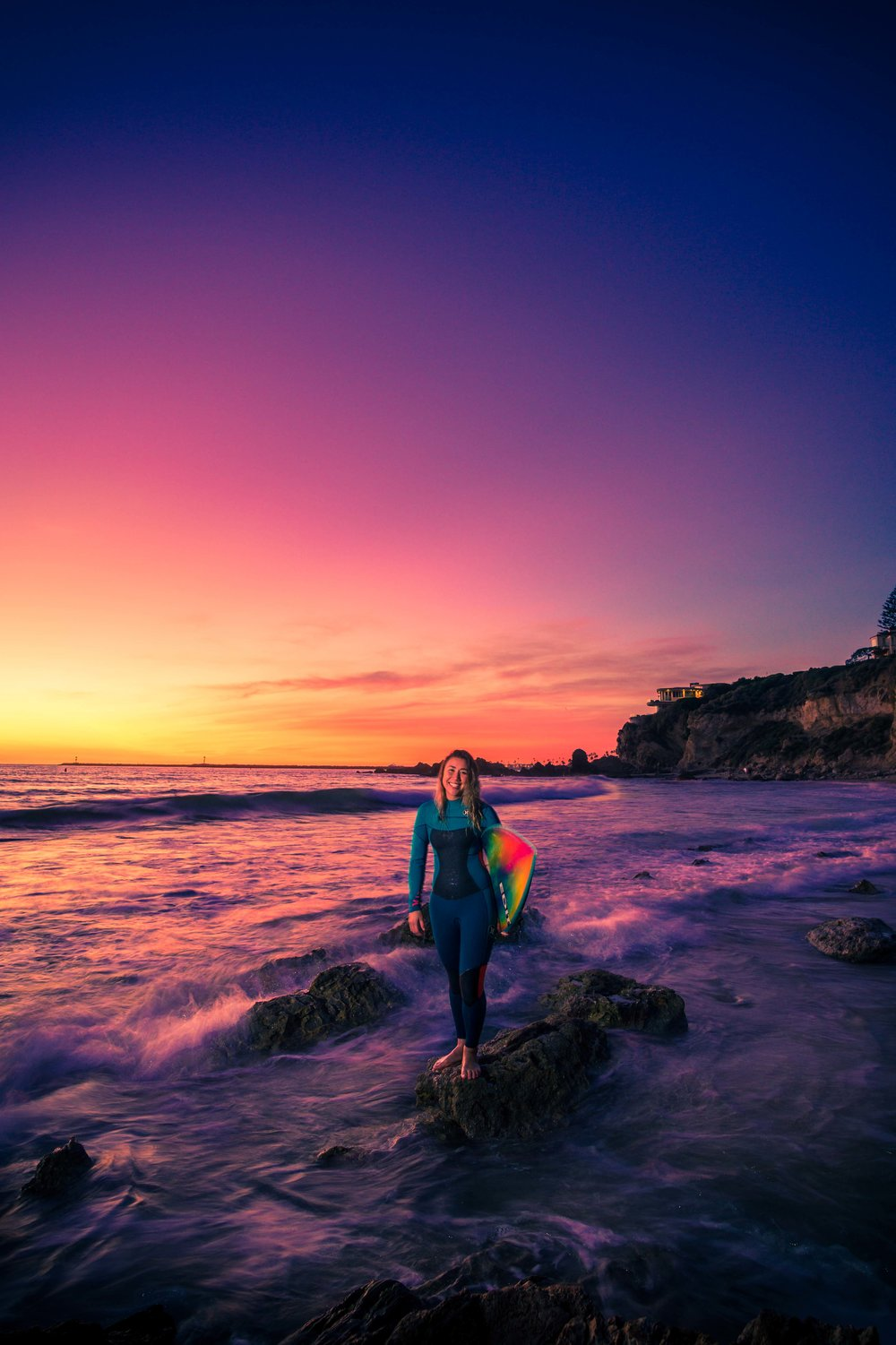 A portrait of a surfer girl at little corona beach with her standing on the tidepool rocks with the waves breaking during a beautiful purple sunset