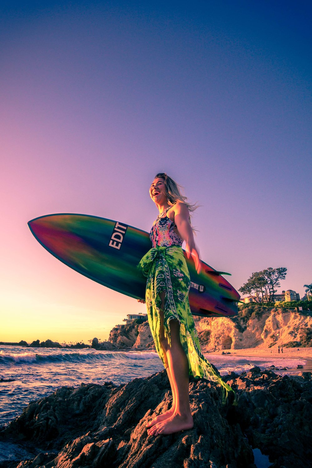 Portrait of a surfer girl with her vibrant attire and hand painted surfboard at the little corona beach