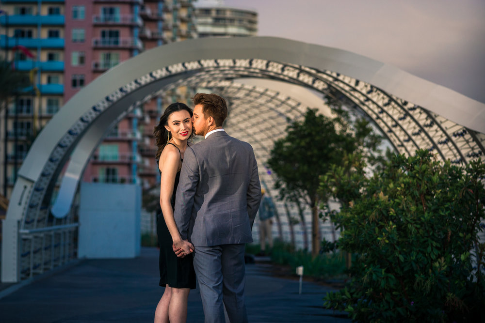 Photo couple Walking under the rainbow bridge To Long Beach convention Center During a couples photo shoot