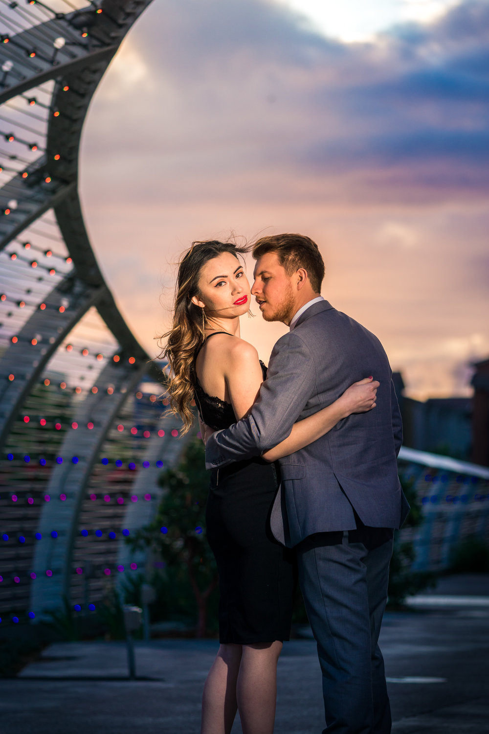 Professional portrait taking a golden hour Of a beautiful Couple Under the rainbow bridge at the Long Beach convention Center