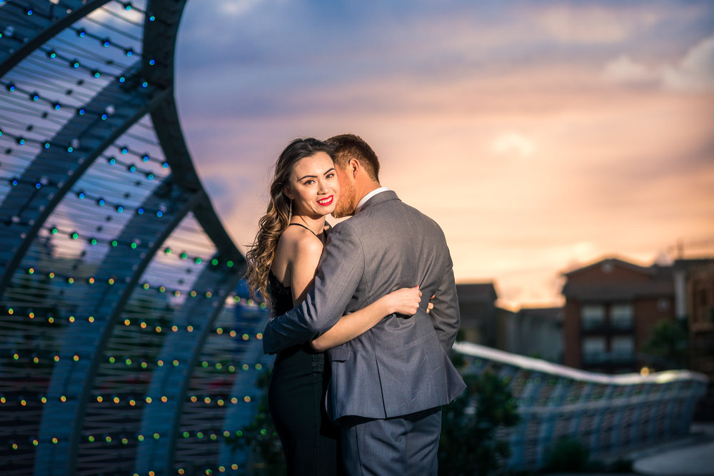 Vibrant and  colorful photo taking a golden hour of a couple embracing at the rainbow Bridge at the Long Beach convention Center