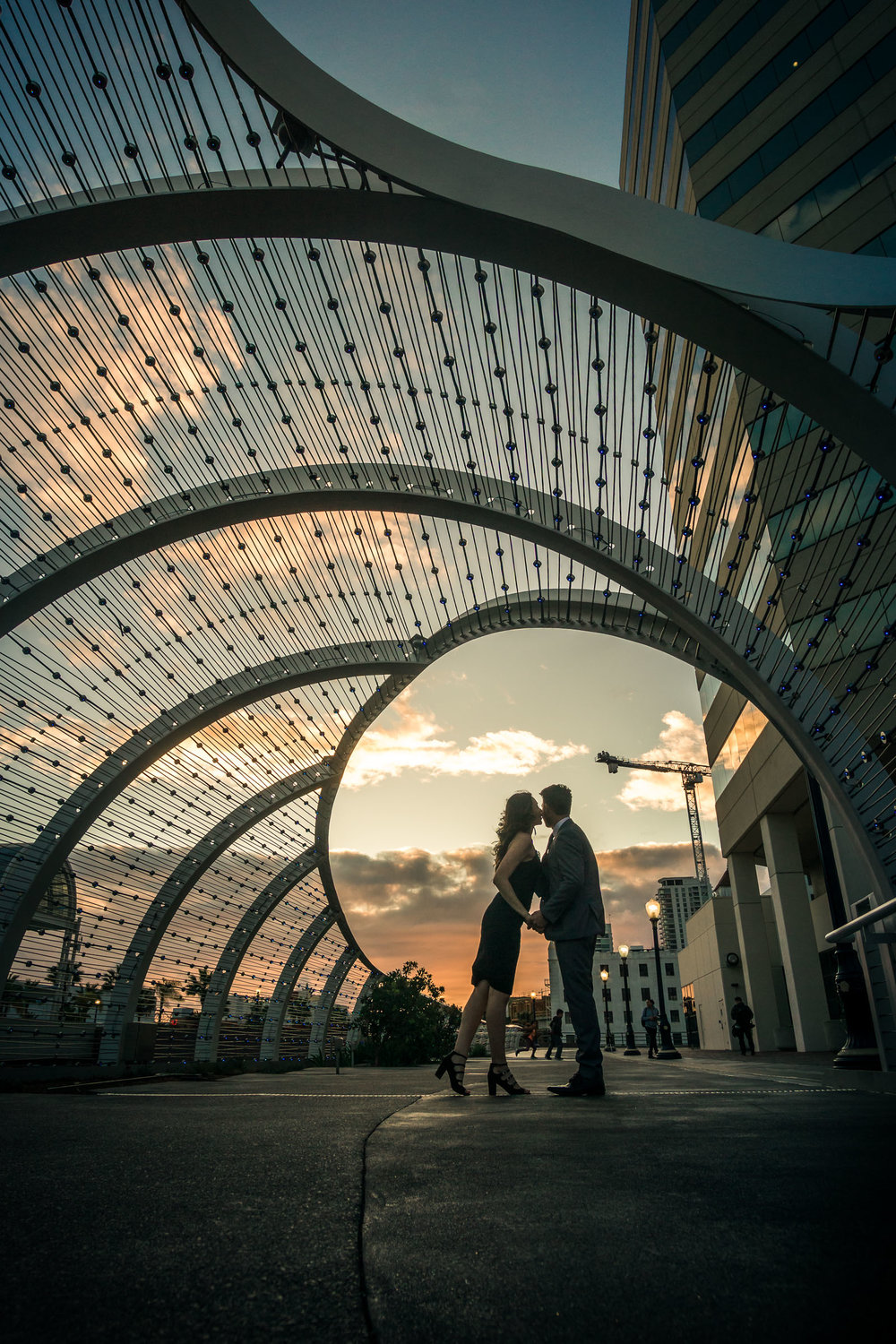 Silhouette of a husband and wife holding hands during a professional portrait photo shoot at the rainbow Bridge At the Long Beach convention Center