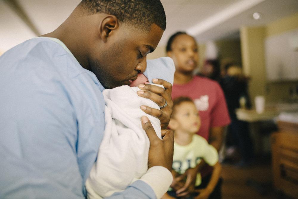 Dad loves on newborn baby