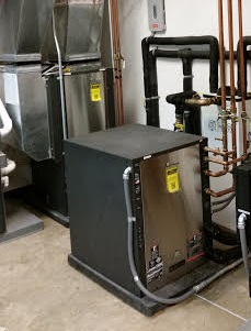 A radiant floor heat pump (foreground) working in conjunction with a forced air heat pump (background)
