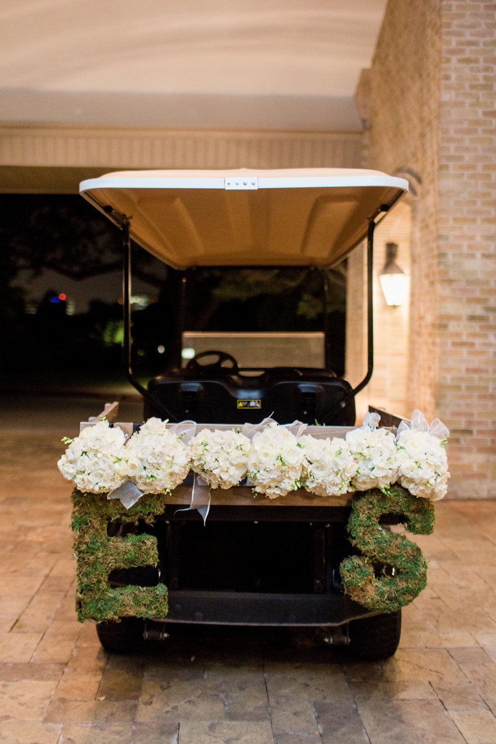 What better way to leave the reception than by golf cart?  Bridesmaids bouquets were repurposed and tied on the back.