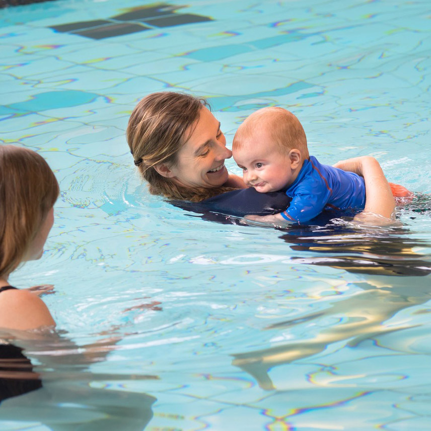 Infant boy smiles as his instructor glides with him through the water.