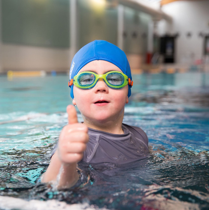 Preschool boy gives a big thumbs up in the pool.