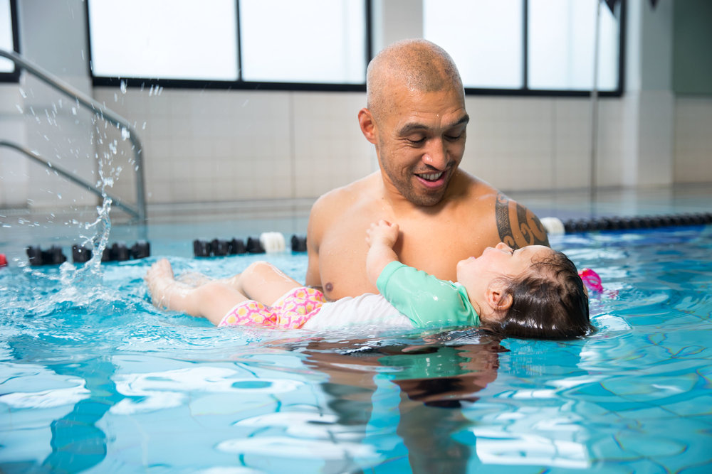 Pre-school child in the pool with her father.