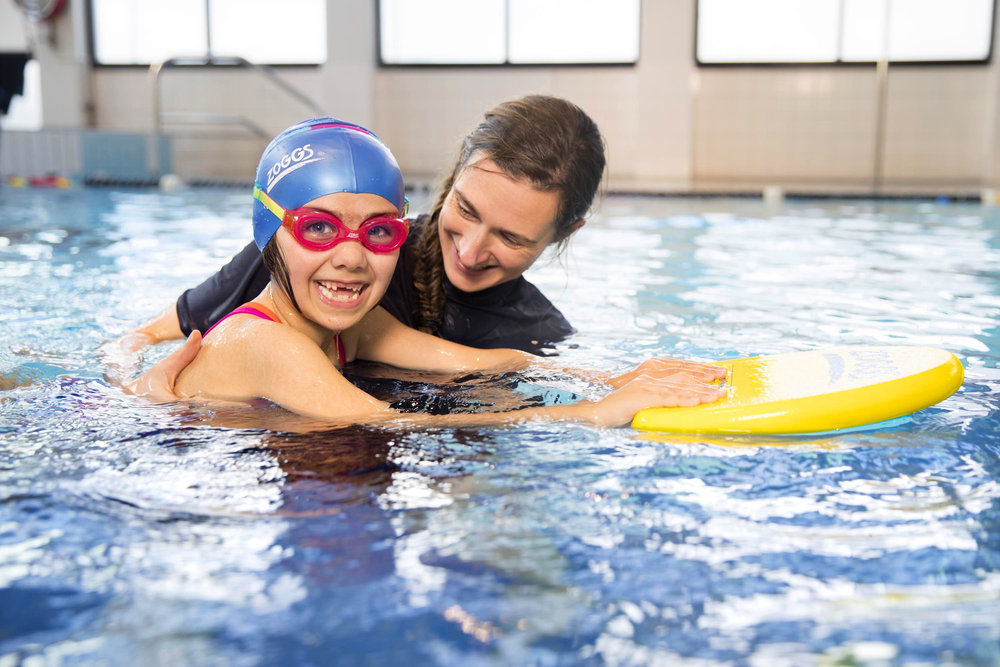 Instructor with school-age child in the pool.