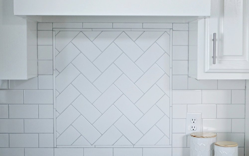 white subway tile herringbone backsplash in this farmhouse style kitchen makeover by Julie Warnock interiors.