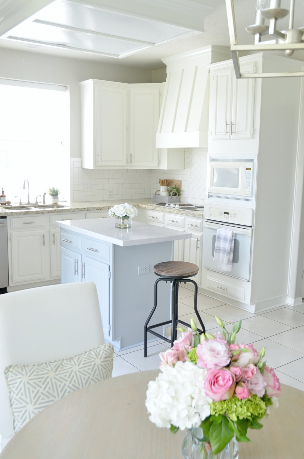 Kitchen Makeover by Julie Warnock interiors features white painted cabinets, subway tile backsplash and custom venthood.