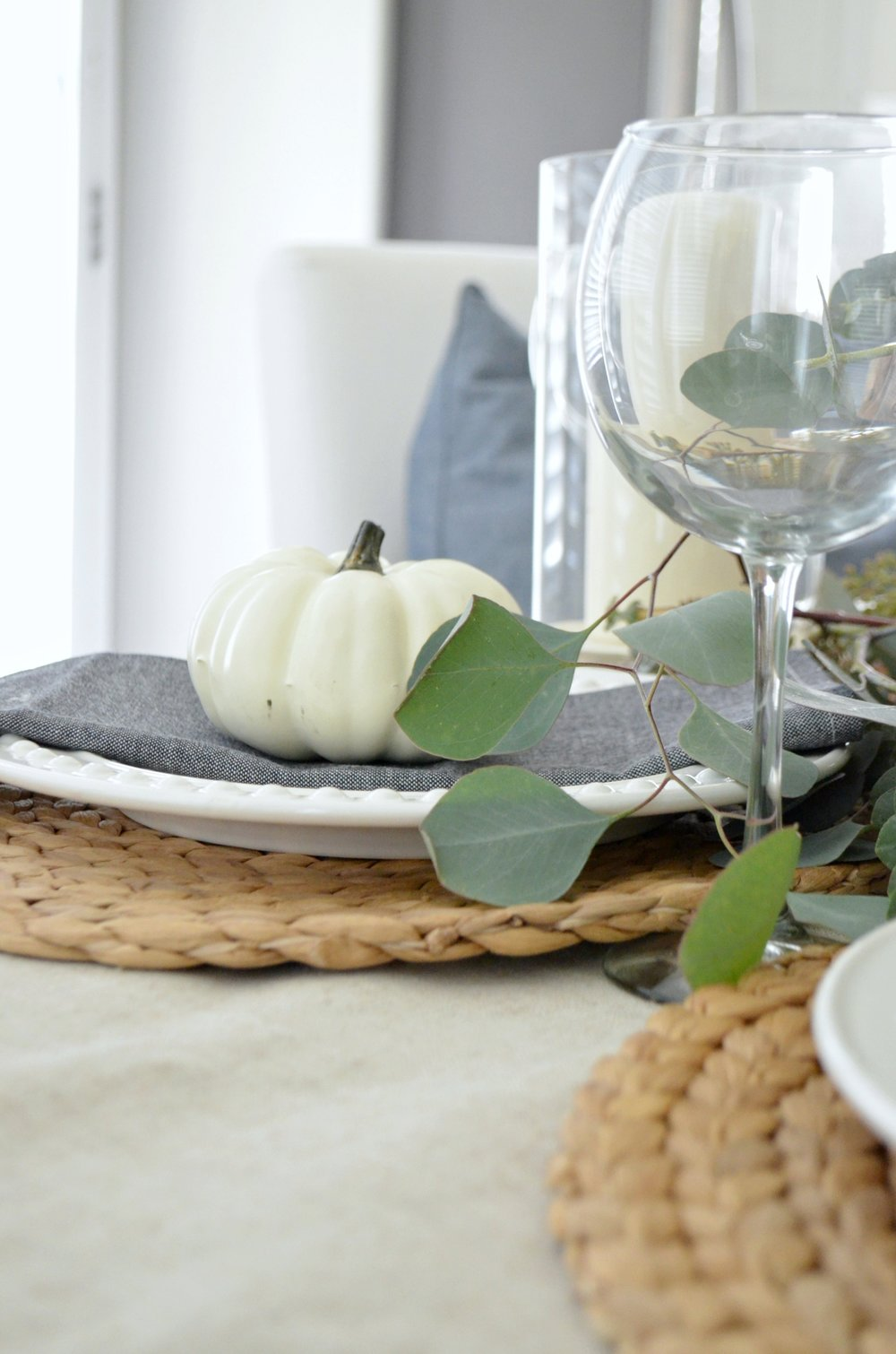 A simple neutral fall tablescape by Julie Warnock Interiors uses white pumpkins, wood tones, and fresh eucalyptus.