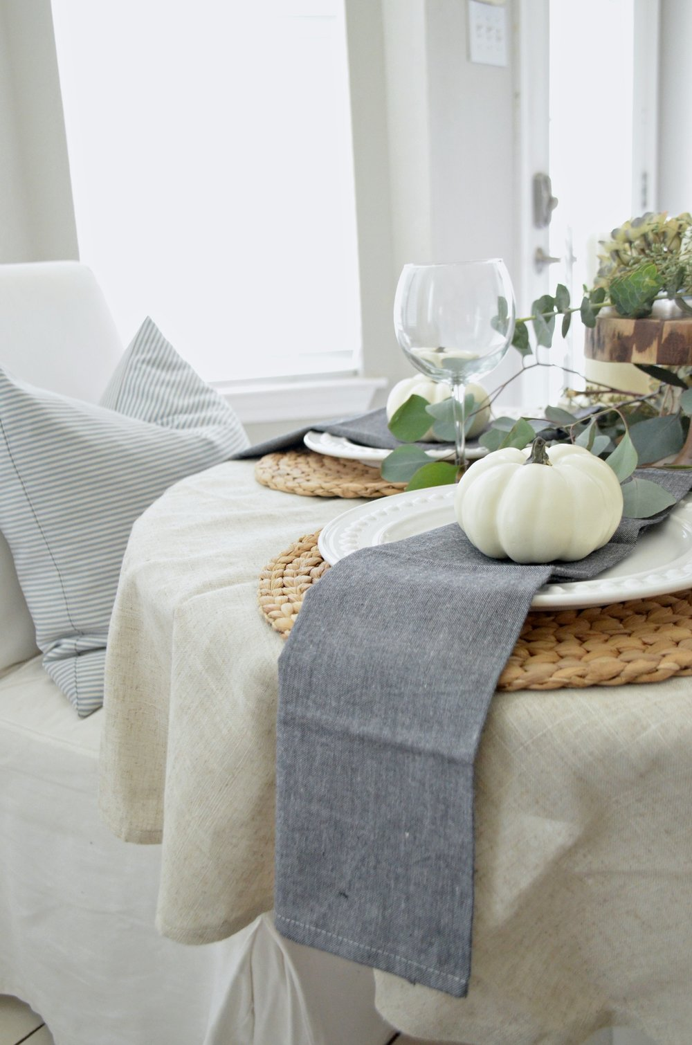 A neutral fall tablescape with white pumpkins and fresh eucalyptus by Julie Warnock Interiors.