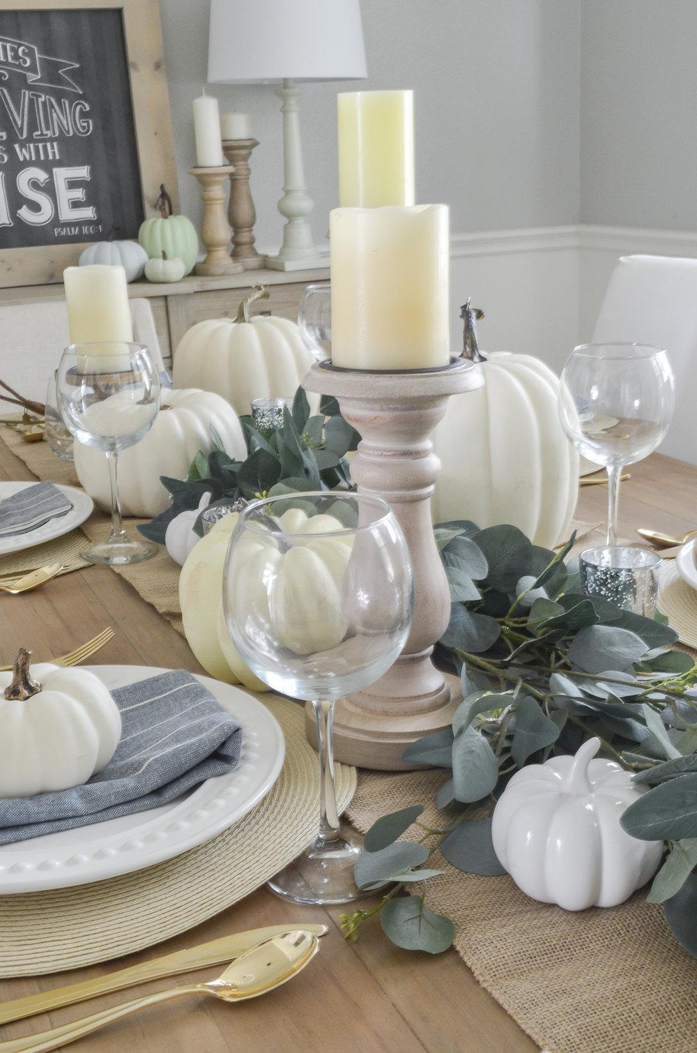 A Simple Fall Farmhouse Tablescape that uses neutral pumpkins, burlap, eucalyptus, and candles.