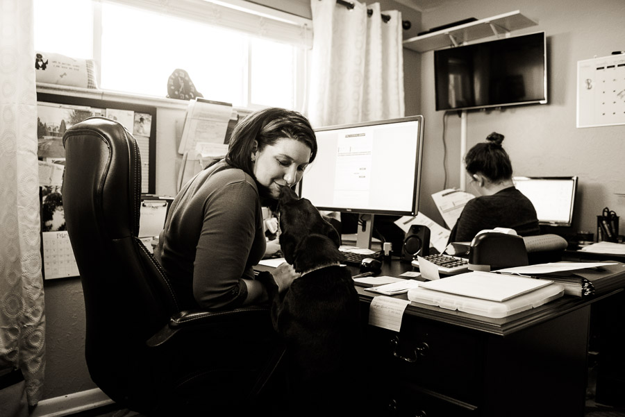 A Day in the Life of a designer - kellie at desk getting dog kiss