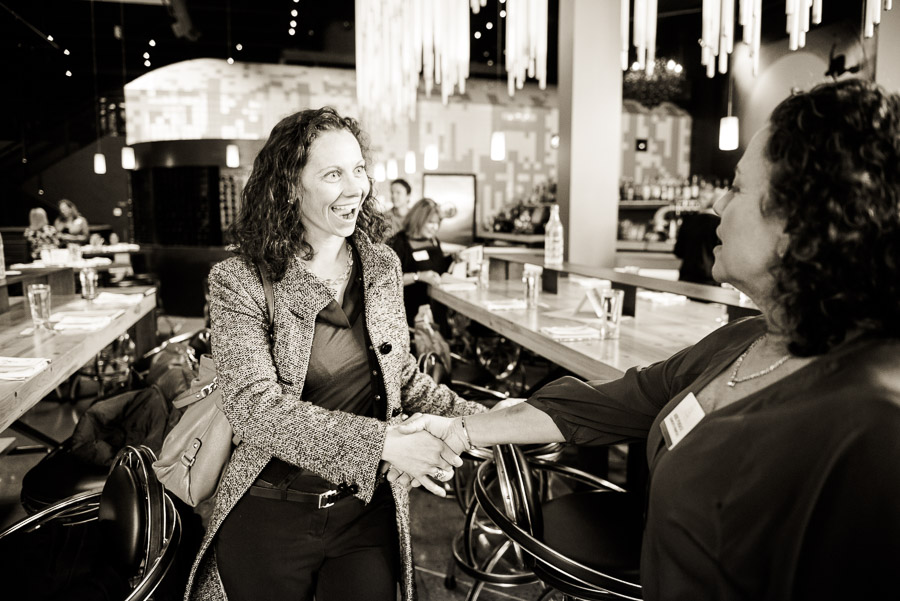 Day in the life of a Denver lawyer - black and white photo of woman shaking hands at an event