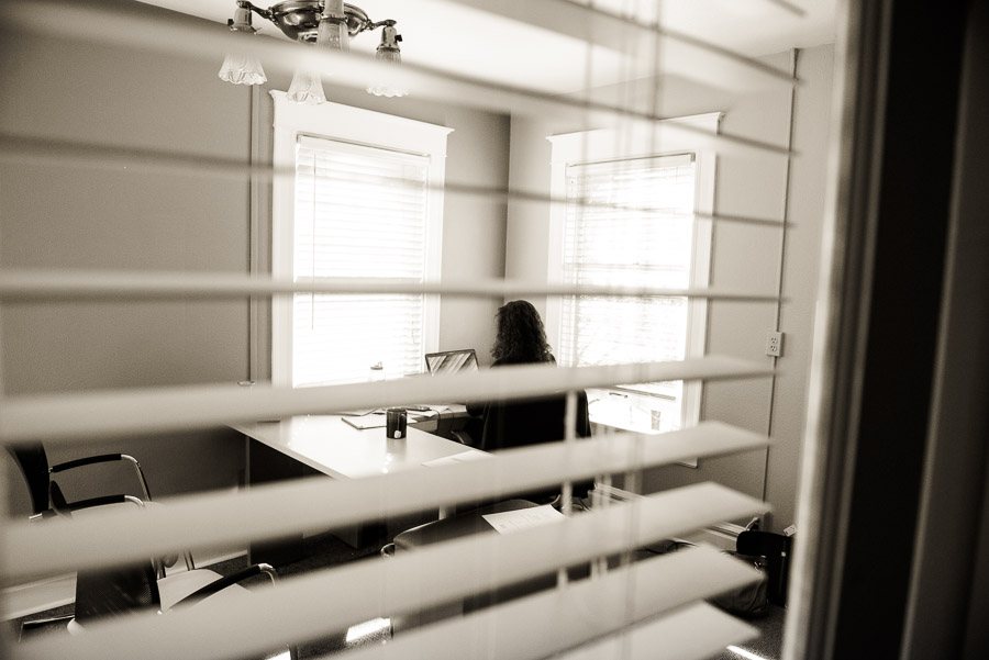 Day in the life of a lawyer - woman at her desk seen through slatted blinds