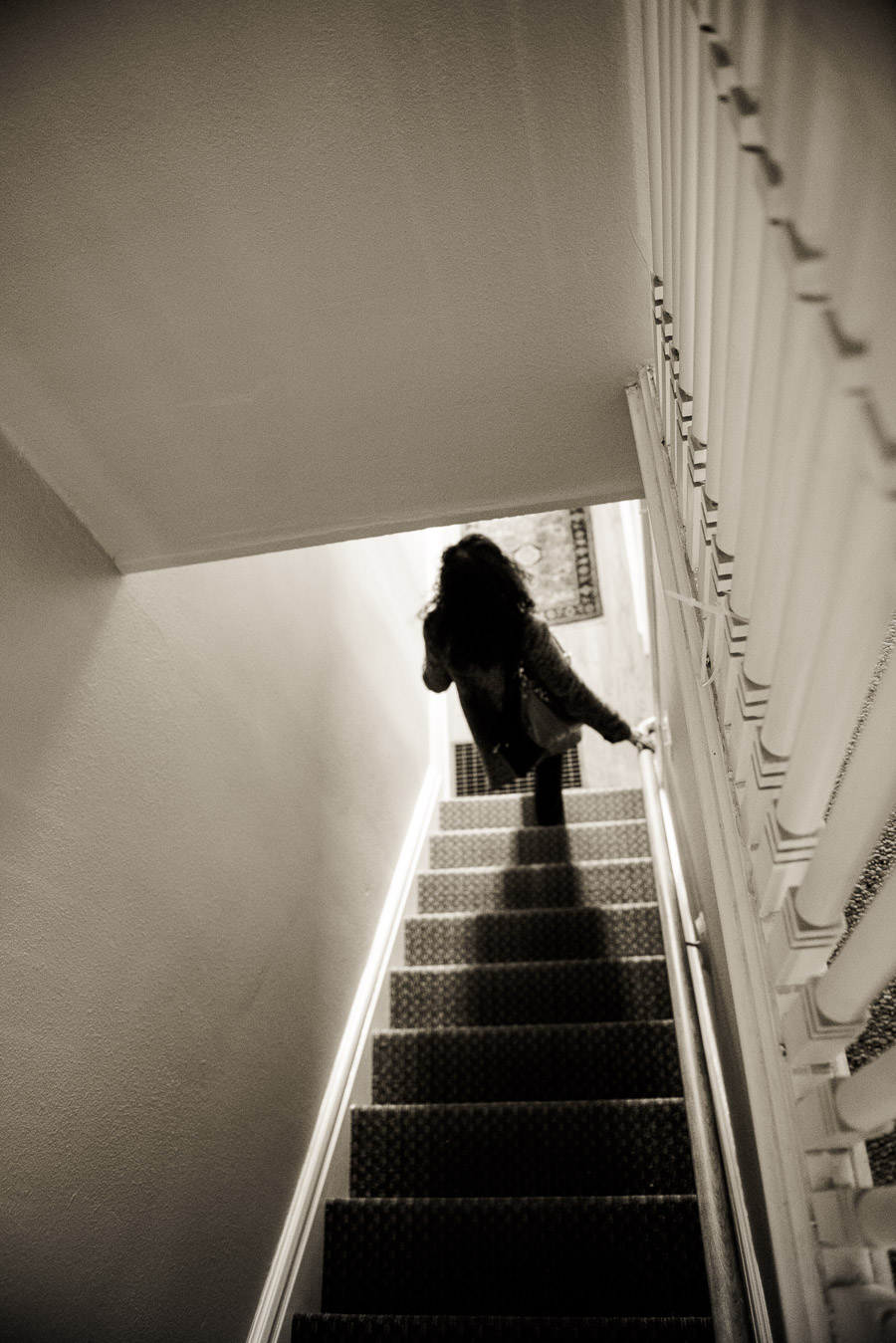 Black and whote of woman going down stairs from above