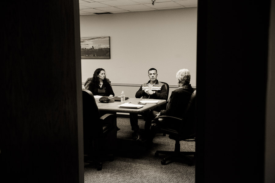 A lawyer, her client, and a mediator through a doorway
