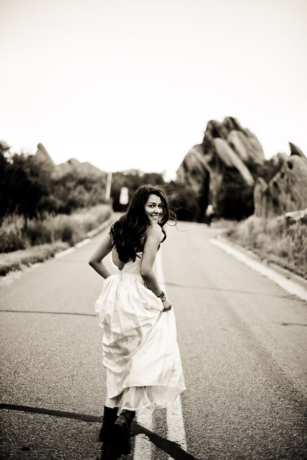 Black and white of teen girl running down the street looking over her shoulder laughing.