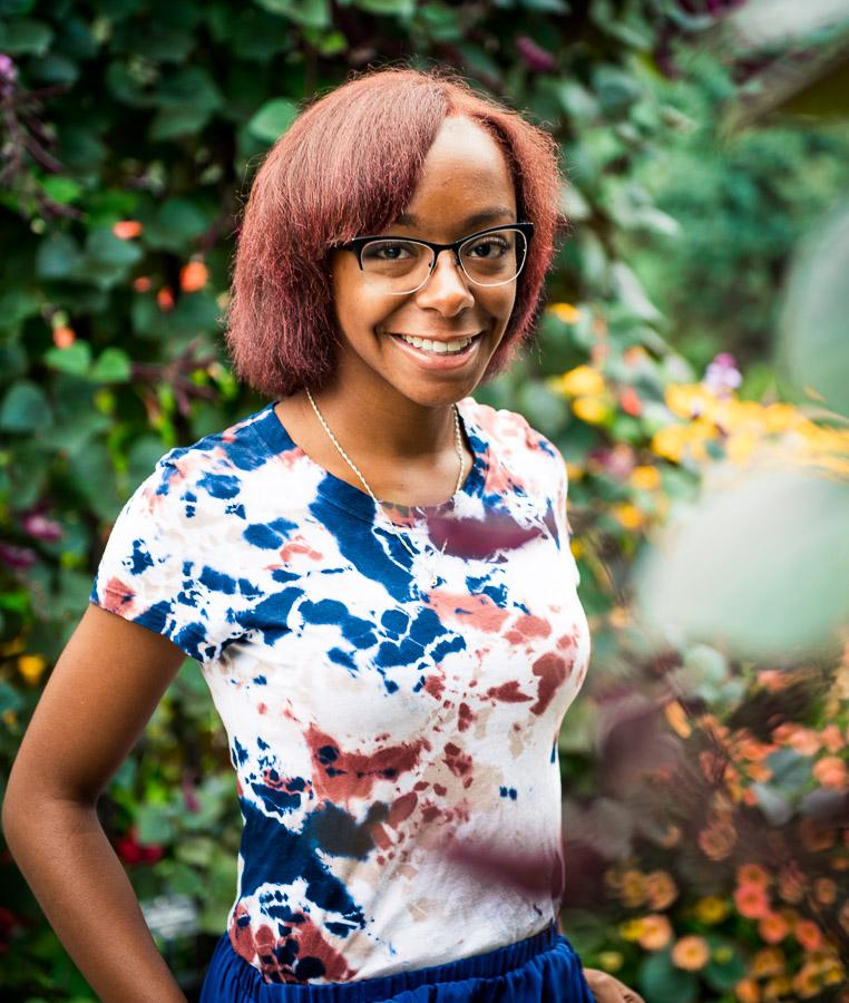 Girl in a tie dyed shirt wearing blasses at the Denver Botanic Gardens