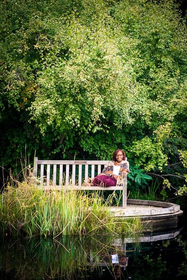 Romantic and remote photo of girl on a bench on a pond seeming far away under a canopy of trees
