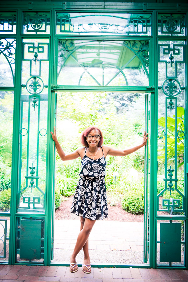 High school senior stands in doorway of solarioum at the Denver Botanic Gardens