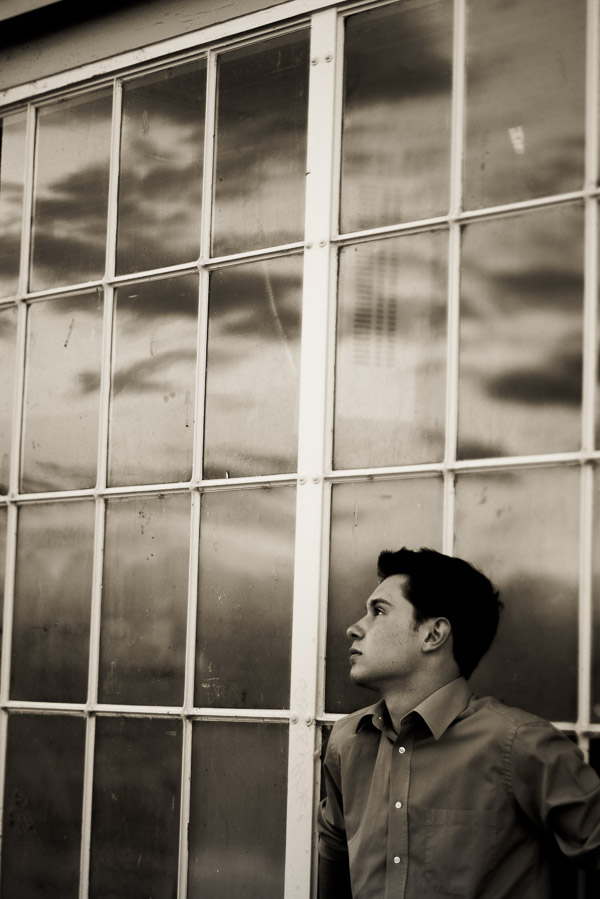 Black and white of teen boy against window reflecting the clouds.