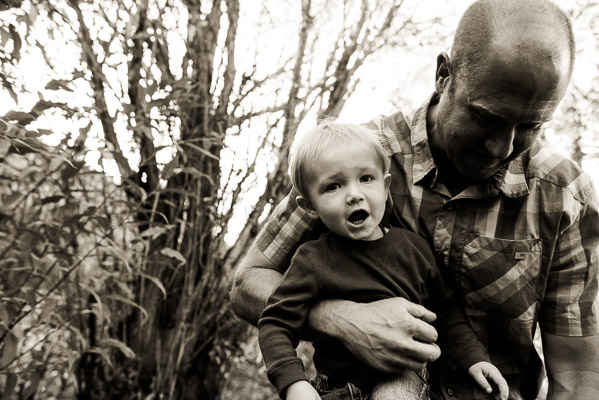 Man in woods holding son and looking away from camera.