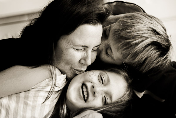 Mom blowing on girl's cheek while son blow's on mom's.