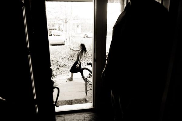 Girl seen outside dancing through the front door.