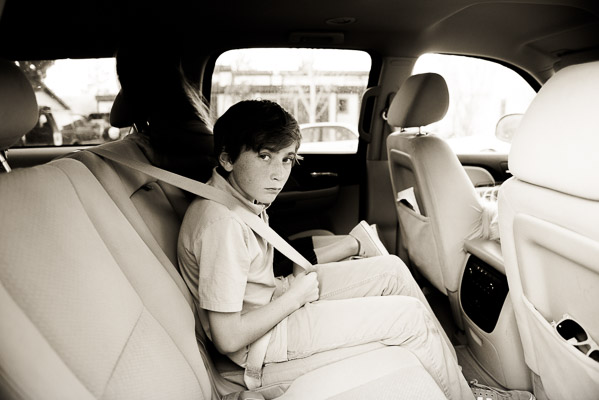 Natural looking photo of boy in car putting on his seatbelt.