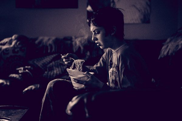Boy eating steaming noodles.