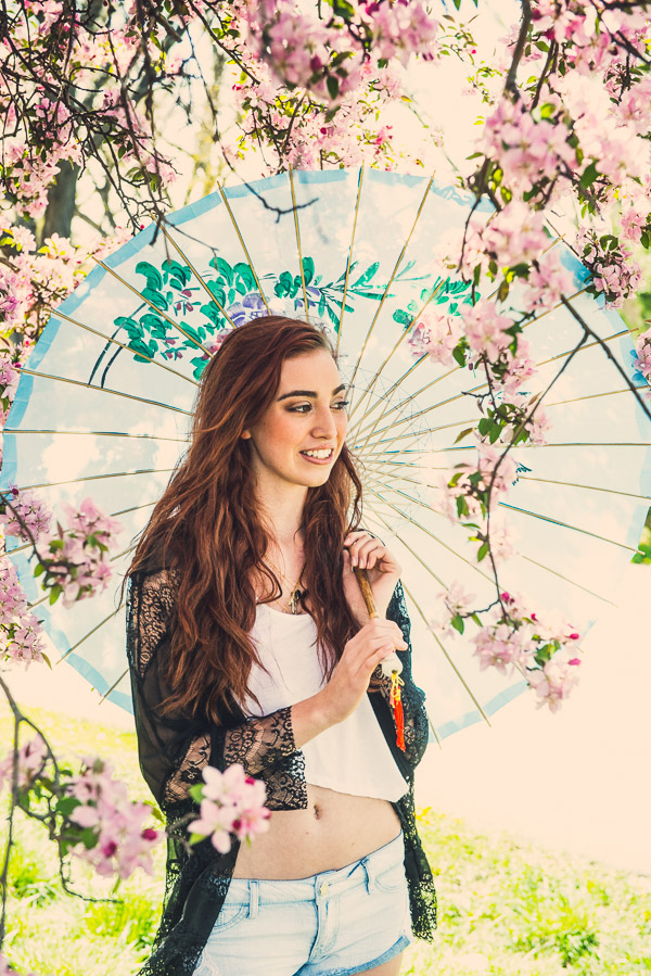 Teen girl looking into the distance holding parasol.