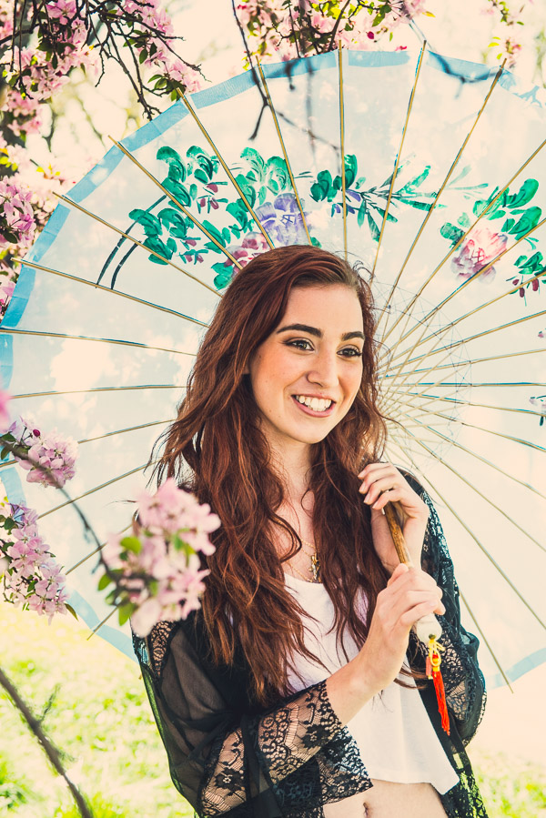 Close up of teen girl holding blue parasol under pink flowering tree.