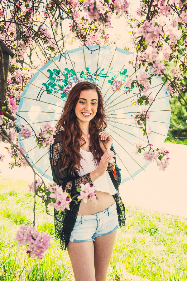 Teen girl under cherry blossoms holding parasol.