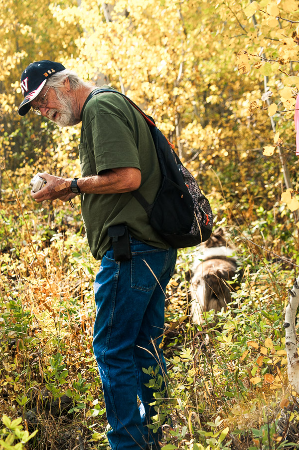 Man wearing baseball cap and backpack in the trees.
