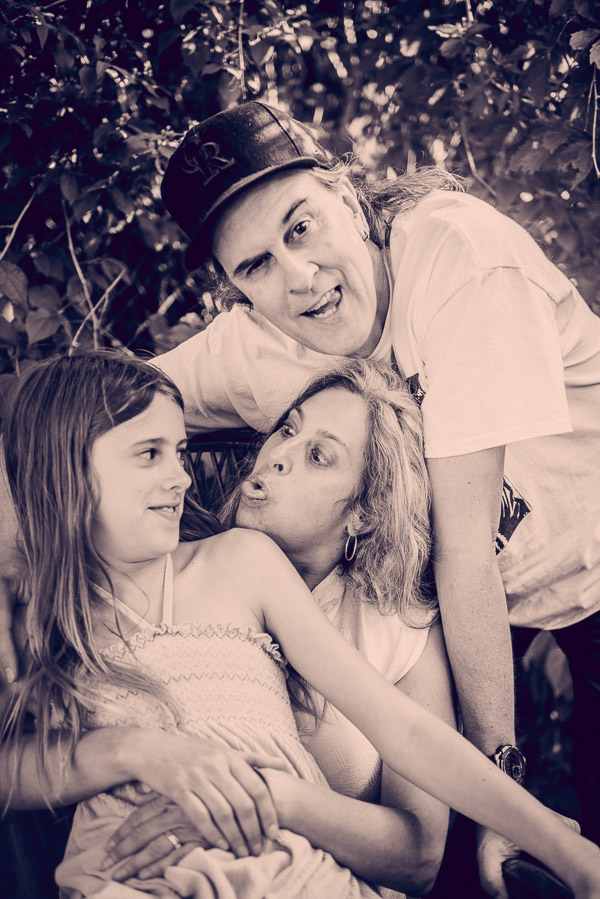 Black and white photo of famly of three all of them making silly faces.