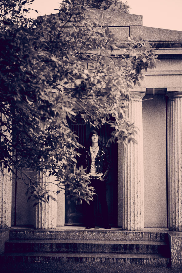 Black and white photo of leather clad boy in front of a mausoleum.