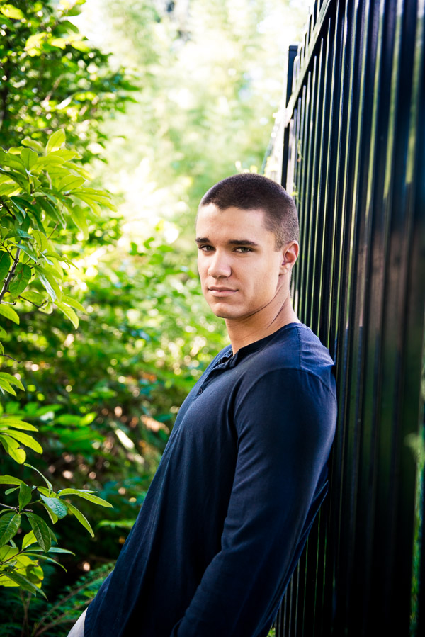 Handsome high school senior leaning on a fence.