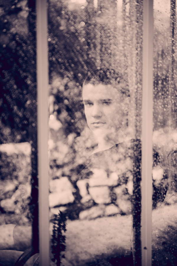 Arty black and white senior photo of boy through wet window.