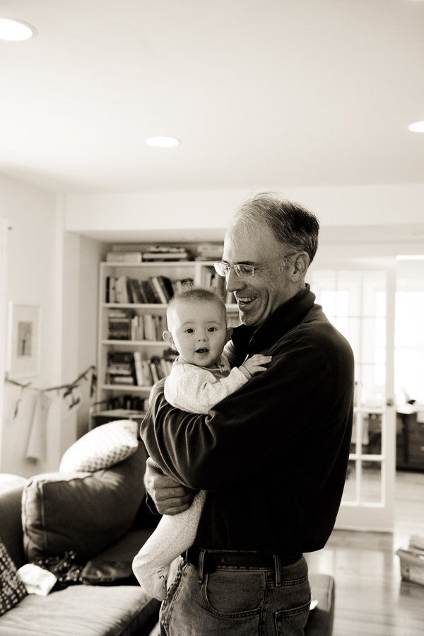 Black and white photo of man holding infant.