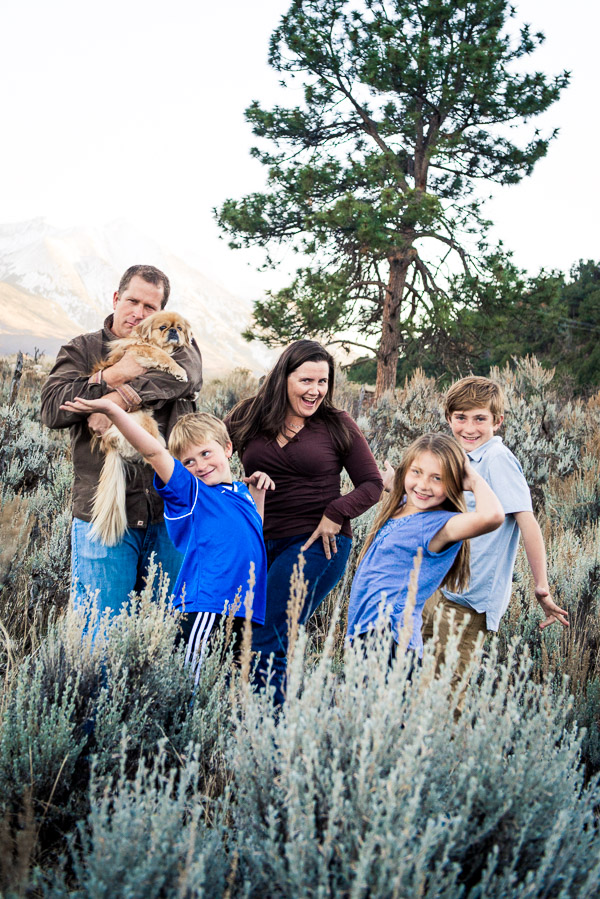 Family strikes a pose in a beautiful field with their dog.