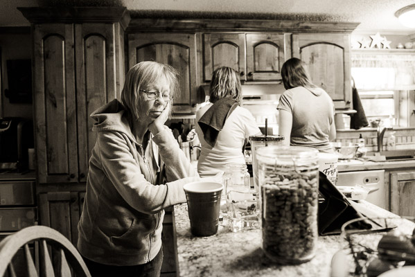 Older woman in a kitchen looking bord while women in background cook.