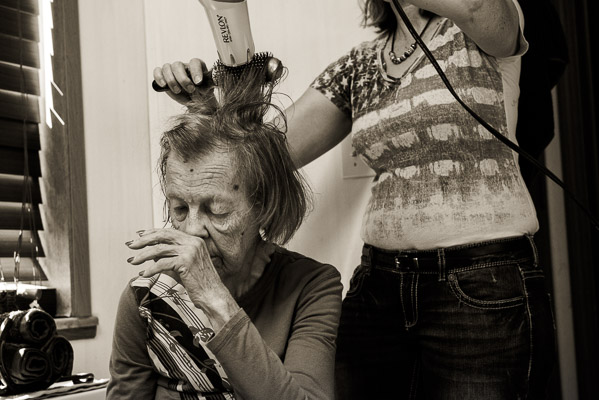 Old woman rubs her nose as another woman does her hair.