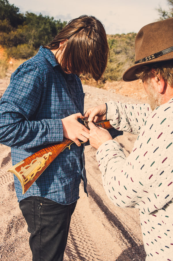 Man loading a black powder rifle with a teen boy.