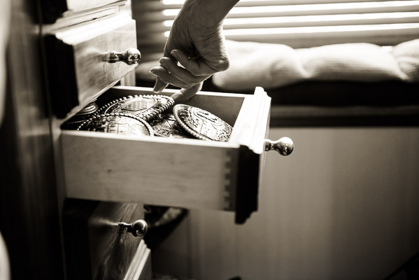 Hands in a drawer full of rodeo buckles.